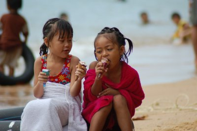 Sisters by the beach enjoying ice-cream