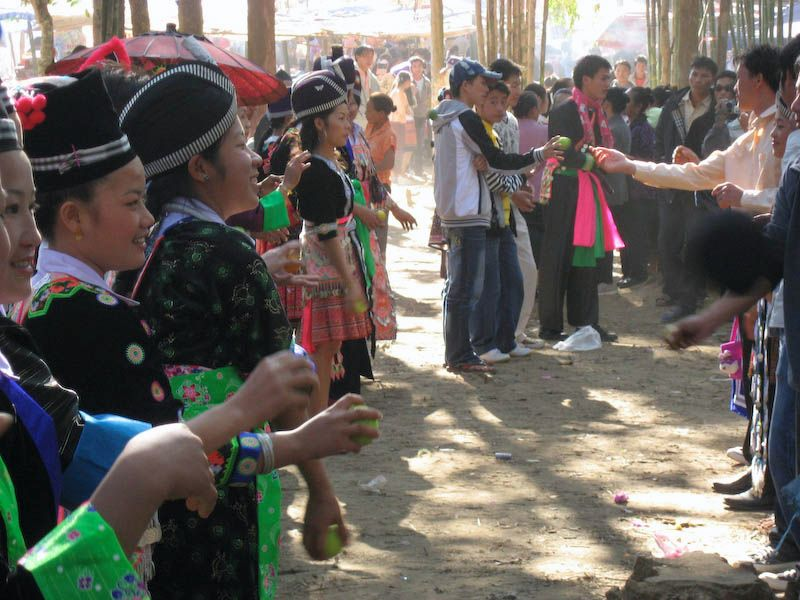 Hmong Villagers throwing tennis balls at each other during new year celebration