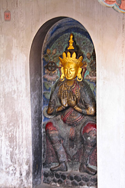 Golden face image next to the giant prayer wheels