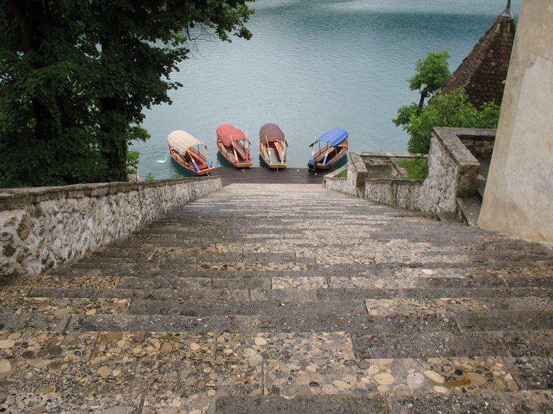 Pletna Boats at the foot of stone steps leading to the island church, Lake Bled, Slovenia