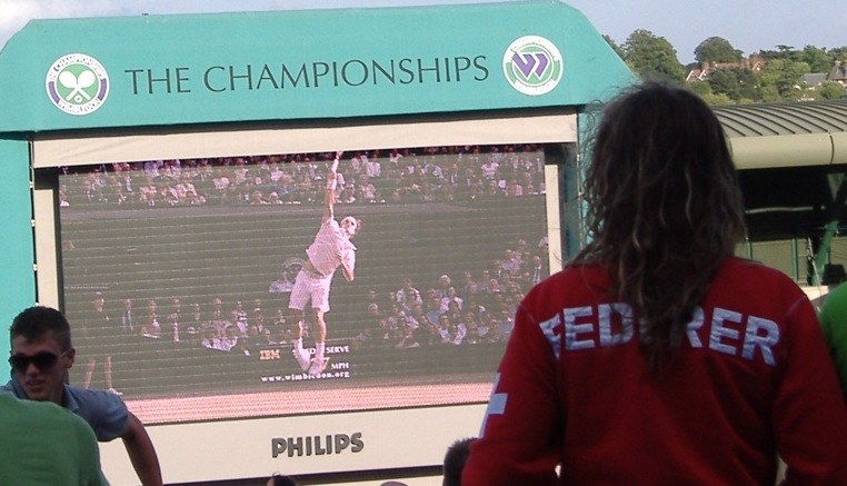 A fan watches Federer on the big screen, Wimbledon