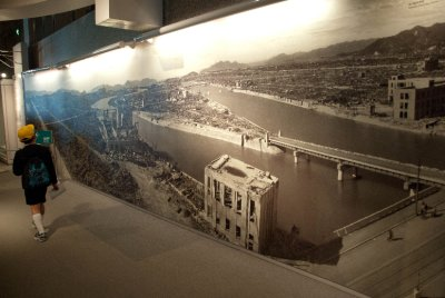A student walks past a mural of the city the day after the the bomb was dropped. You can see the A-Bomb Dome next to the student (click on the picture for a larger image). Next to this mural is the city, full of houses, the day before the bomb was dropped. Hiroshima was almost completely leveled, with just a few structures left standing.