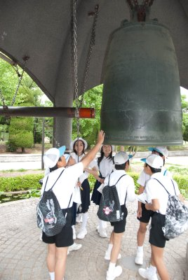 Kids ring the peace bell.
