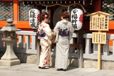 Women dressed in traditional kimonos visit a shrine at the Kiyomizu-dera Temple.