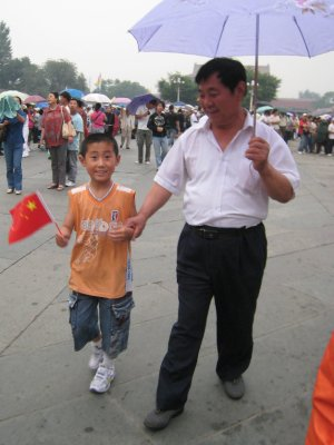 A boy and his father smile for the camera as they enter the Forbidden City.