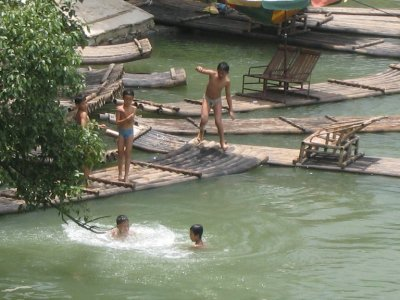 Children swim in the murky river to cool off.