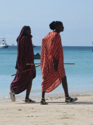 """Faasai are fake Maasai. They are dressed similarly to Maasai, with their wool blanket, lion sword, and staff, but they have the tell tale fancy watch, sunglasses and sandals. They wander the beaches making money for photo opportunities and """"massages,"""" an apparent cover for prostitution. More on the real Maasai people below."""