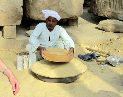 A worker sifting through the sand.