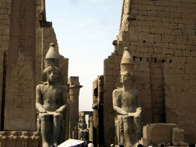 Two remaining large statues of Ramses ll. Four others were never found. Note the crevices in the pylon wall which would have held cedarwood masts, flying pennants.