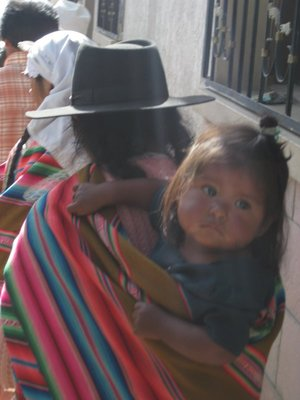 Bolivian women in traditional dress with child
