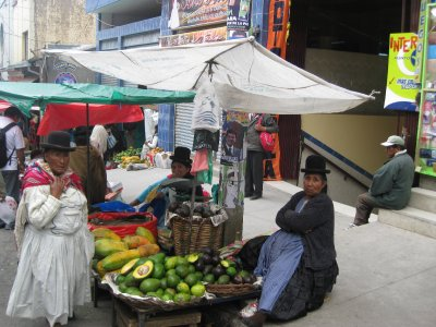 Ladies in traditional dress selling fruit - note the Bowler hats that are too small and just balance on their heads, Josh is fascinated by these!