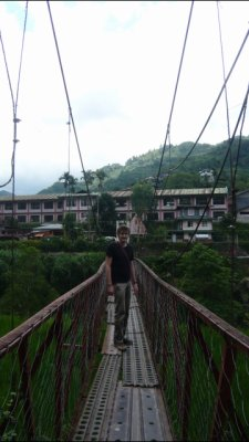 Adam walking over rickety Banaue Bridge
