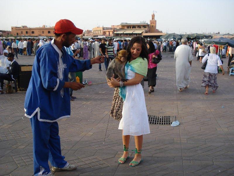 She's Holding a Monkey in Jemaa el Fna Market