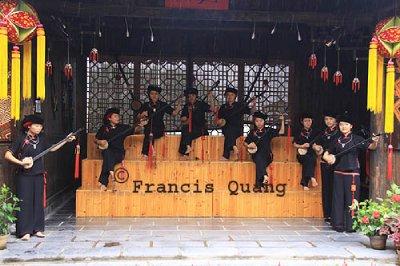 Female Zhuang minority group playing traditional stringed musical instrument ,Yangshuo, Guangxi, China