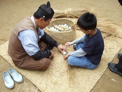 Man demonstrates weaving to child in South Korea