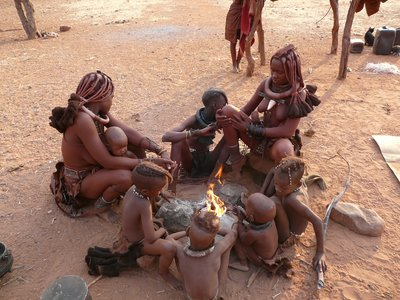 Himba family warming by the fire