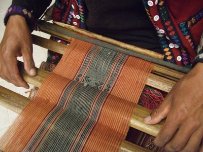 Traditional weaving using a belt loom at the textile centre in Cusco