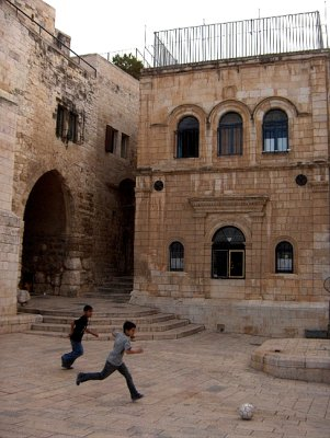 Kids playing football in courtyard