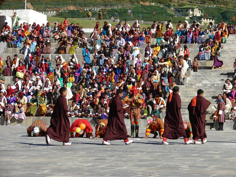 Clowns bowing to a procession of monks at the opening of Thimphu Tsechu