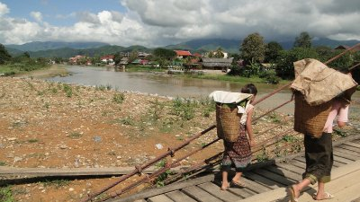 Local ladies crossing a bridge in Vang Vieng