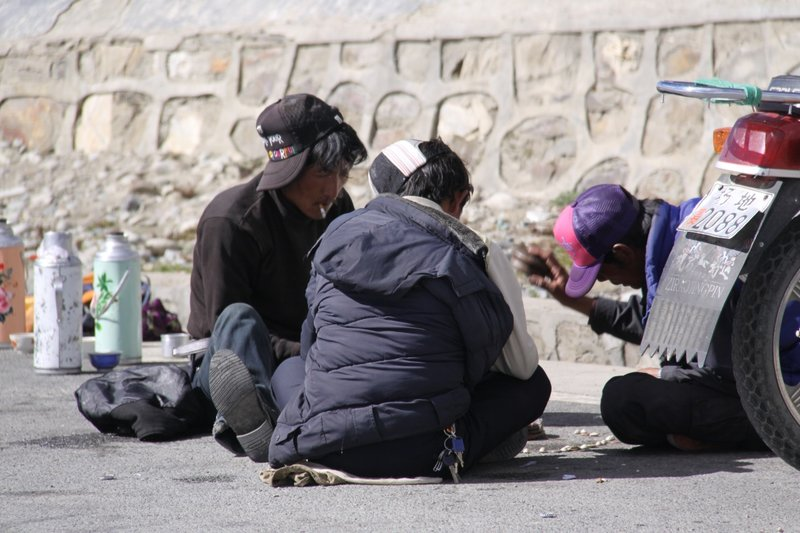 Tibetans playing a game on the road above Yamdrok lake.