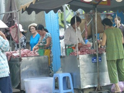 Ladies in pyjamas buying and selling meat