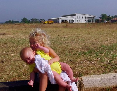 Amelie and Asher with new airport terminal behind them. How will the airport be changing over the next few years?
