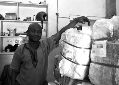 Robert poses by a 45kg bale of clothing from Raghvani texties in India