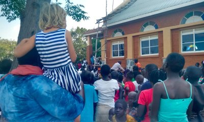 Amelie being held aloft by a teacher at a Sunday school Christmas event