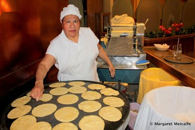 Lady making and cooking tortillas