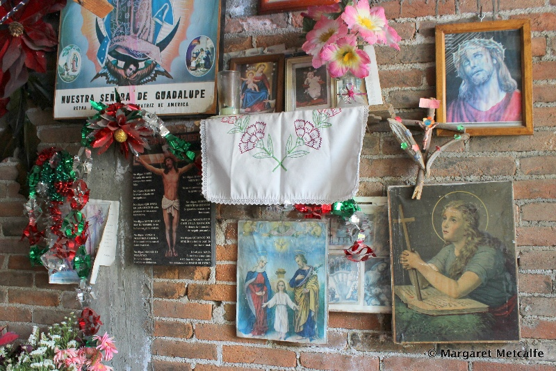 Religious artifacts on wall near weaving loom