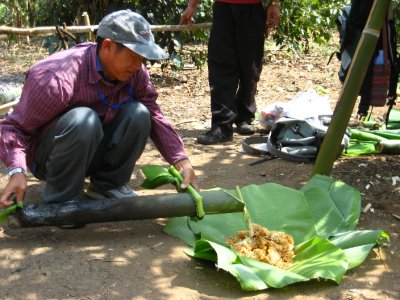 Pouring the vegetables over the noodles in a banana leaf bowl