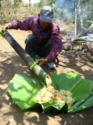 Pouring the vegetables over the noodles in the banana leaf bowl
