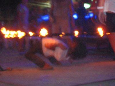 A guy limboing under fire on Ko Phi Phi Beach