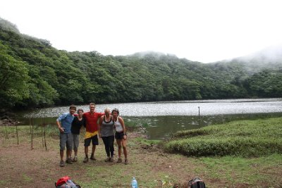 The group posing up in front of the lake in the crater on top of the volcano