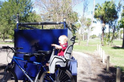 Isaac hitches a ride on the bike and trailer
