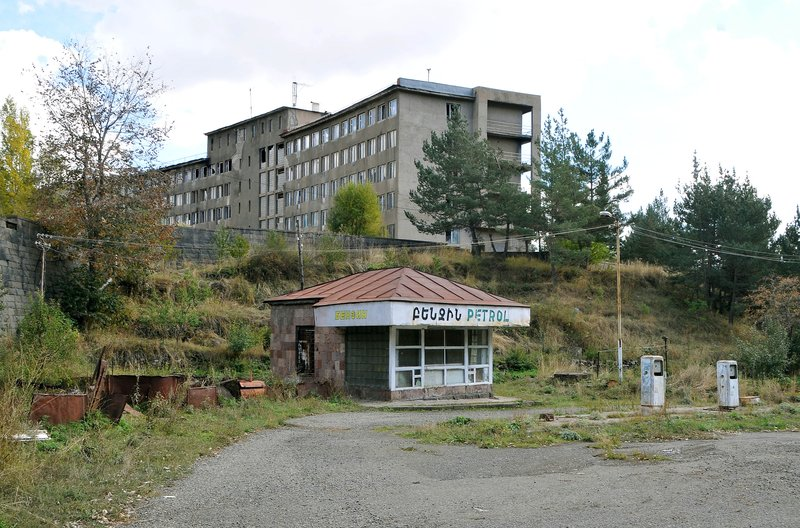 old  petrol station with ex-soviet hotel behind