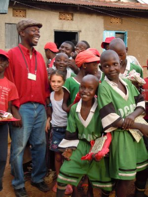 Brooke is surrounded by smiling black faces and converses in French with Papa who runs the orphanage (the one with the plaid cap)