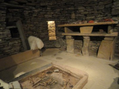 Reconstruction of inside of house showing dresser, bed on left, cupboards set into the wall, and hearth