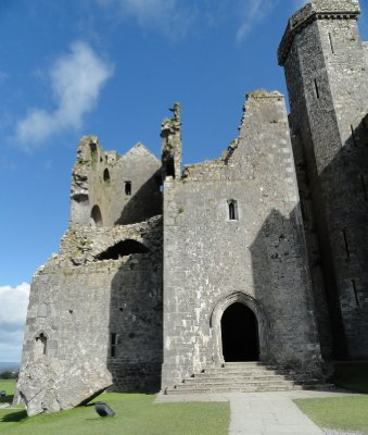 Fortified tower house with part of fallen tower on the ground on left.