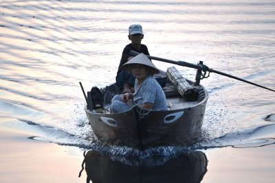 A young boy rows his boat to shore