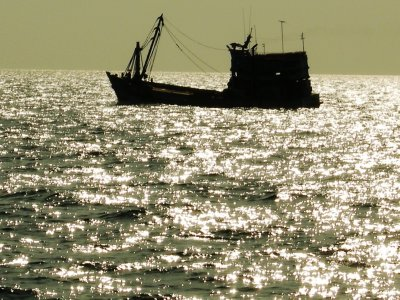 A fishing boat silhouetted against the diamond seas near Angthong