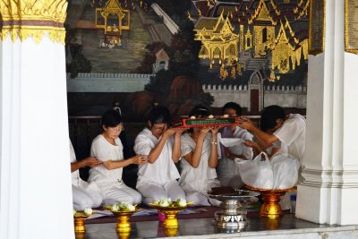 Women chant prayers and bless offerings to Buddha