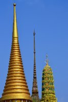 The golden tops of a stupa and a temple glint in a brilliant blue Bangkok sky