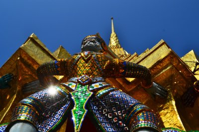 An exquisitely decorated demonic figure glints in the sunlight at the base of a golden stupa in Wat Phra Kaeo, Bangkok