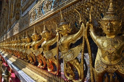 A long row of gilded demons decorate a building in Wat Phra Kaeo, Bangkok
