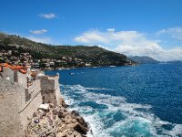 City Walls on Dubrovnik's coastline - there is a bar on the rocks in the foreground.