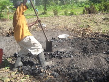 Getting the freshly made charcoal out of the dirt mound