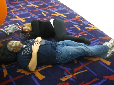 Jen and Andy sleeping on the floor at the airport