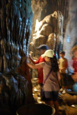 Her gnir buddhistene penger mot en stalakit for å få lykke i form av mere penger......